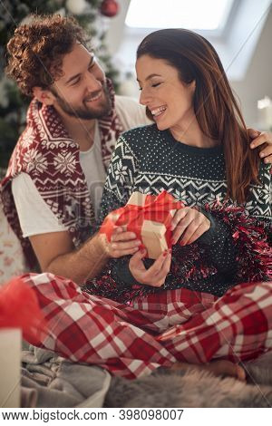 A young couple in love spending a Christmas morning at home sharing presents in a relaxed atmosphere. Christmas, relationship, love, together