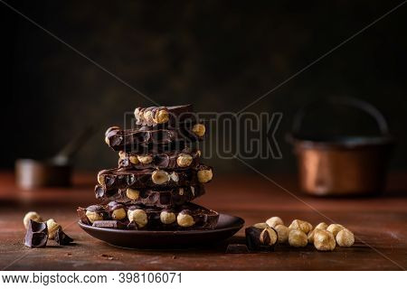 In The Foreground Some Stacked Pieces Of Dark Chocolate With Hazelnuts. Composition And Dark Brown B