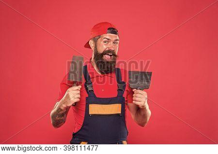 Plasterer Hipster Builder In Cap Red Background. Interior Designer. Bearded Man Worker With Plasteri