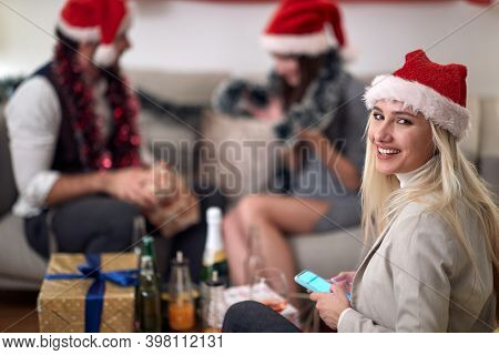 portrait of young caucasian blonde smiling with santa hat, looking at camera, holding cell phone, with friends in the background. christmastime