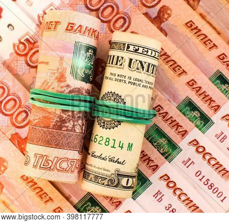 American Dollars And Russian Rubles Rolled Up In A Tube. Currency Exchange Rate. Ruble Devaluation C
