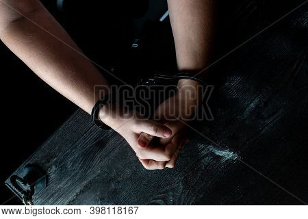 A Man With Hands In Handcuffs At Table, Concept. The Hands In Handcuffs Squeeze And Unclench Hands,
