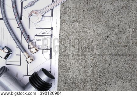 Top View Of Plumbing Equipment And A Blueprint Project On A Concrete Floor Background With Copy Spac