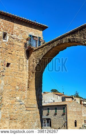 Historic Tenement House And Fragment Of An Ancient Stone Aqueduct In Pitigliano, Italy