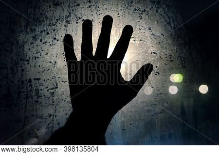 Help Me Please. A Hand Calling For Help On The Blurry Foggy Night Glass Window. Symbol Of Helplessne