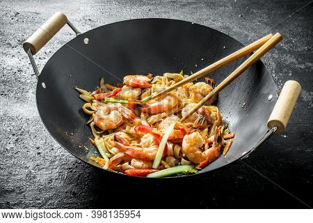 Hot Chinese Wok Udon Noodles With Sauce, Shrimp And Vegetables. On Rustic Background