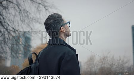 Man In Black Coat Walk On Background Of Business Skyscrapers, Slow Motion. Gimbal Profile Shot Of Bu