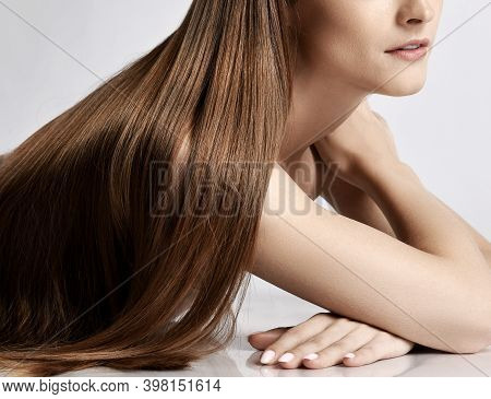 Close-up Of Silky Long Straight Hair Of Young Beautiful Woman Model Lying And Posing Over White Back