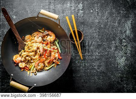 Freshly Cooked Asian Udon Noodles In A Wok Pan With Soy Sauce And Chopsticks. On Dark Rustic Backgro