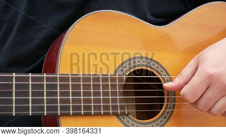 Acoustic Guitar Arpeggios. Man Playing Guitar Outdoors On The Acoustic Western Guitar With Steel. Ro
