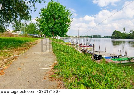 Footpath Is Placed By The River And Fishing Boats Are Anchored On Improvised Dock In The Shallow Wat