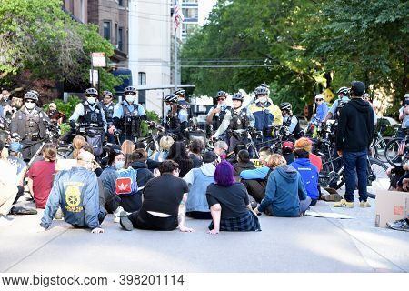 Chicago, Il June 14, 2020, Young People Sitting Down On The Street With Chicago Police Bike Cops Blo