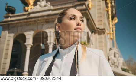 Portrait Of Posh Woman Intently Looking Away With Beautiful Old Architecture On Background