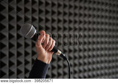 Woman Hand Holding Vocal Mic On Acoustic Foam Panel Background
