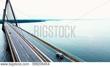 Large Highway Bridge Spanning Over A Bay, With Cars And Trucks Driving. Aerial View.