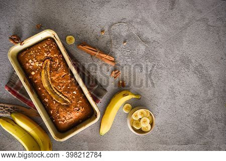 Freshly Baked Multigrain Banana Bread  On Grey Background With Banana, Cinnamon And Nuts. Bake Shop,
