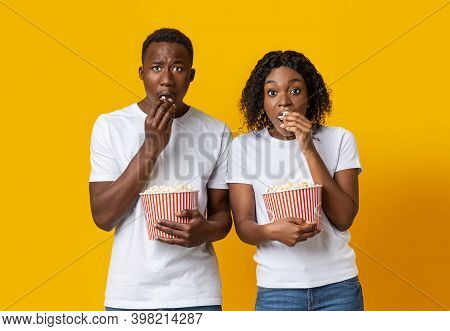 Shocked African American Couple With Popcorn Watching Spooky Movie, Yellow Studio Background. Astoni