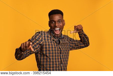 Hey, You. Emotional Black Guy Pointing Fingers At Camera With Both Hands Standing Over Yellow Backgr