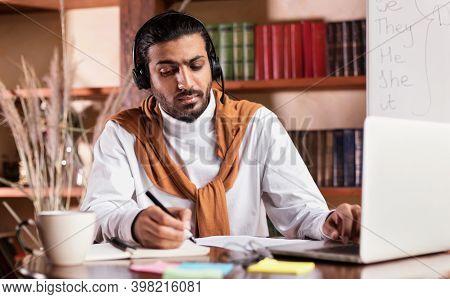 Online Teaching. Arab Male Teacher Sitting At Laptop Wearing Headset And Taking Notes Having Remote