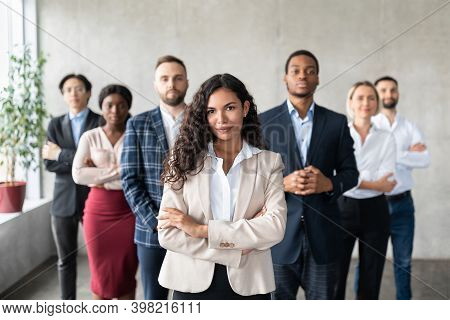 Successful Latin Businesswoman Standing In Front Of Business Team Posing In Modern Office, Smiling T