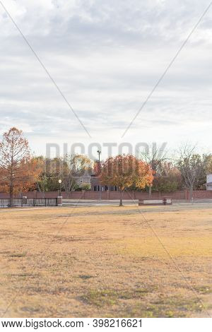 Sunset Over Park Meadow With Colorful Fall Foliage And Row Of Upscale Houses Near Dallas, Texas, Usa