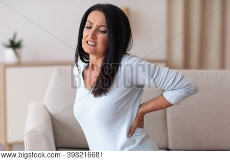 Portrait Of Sad Mature Woman Having Back Pain While Sitting On The Couch At Home, Suffering From Ten
