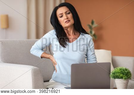 Tired Of Work. Portrait Of Mature Lady Having Back Pain While Sitting On The Couch At Home, Sufferin