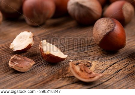 Hazelnuts In On Rustic Background. Pile Of Hazelnuts. Whole And Opened Hazelnuts. Hazelnut Close-up.