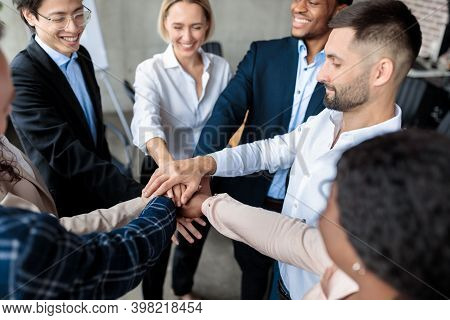 Happy Coworkers Holding Hands Standing In Circle During Corporate Teambuilding Meeting In Modern Off