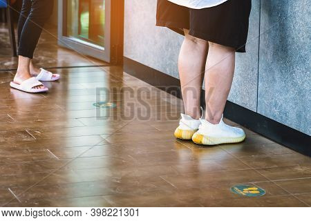 Feet Of Customers Waiting To Order Food With Stand Here Foot Sign Or Symbol On The Wooden Floor In C