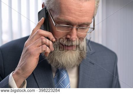 An Adult Gray-haired Respectable Man Discusses Business On The Phone. The Boss Calls On The Phone An