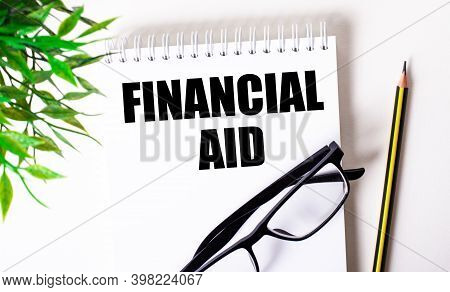 Financial Aid Is Written In A White Notebook Next To A Pencil, Black-framed Glasses And A Green Plan