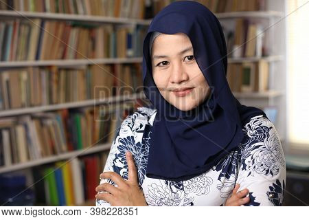 Portrait Of Cheerful Asian Muslim Female Librarian Wearing Hijab, Looking At Camera And Smiling Cros