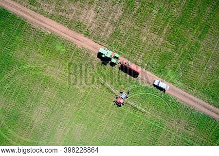 Treatment Of The Field With Herbicides. A Tractor With A Spray Gun Drove Up To A Tractor With A Barr