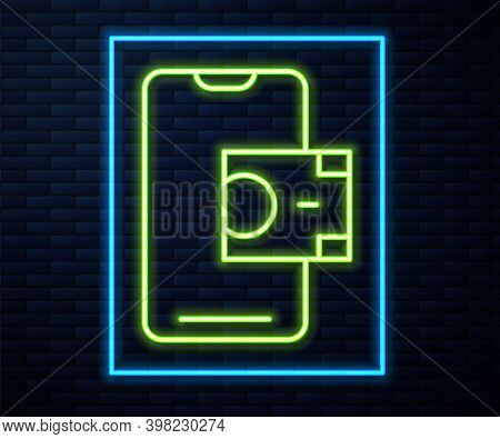Glowing Neon Line Mobile Banking Icon Isolated On Brick Wall Background. Transfer Money Through Mobi