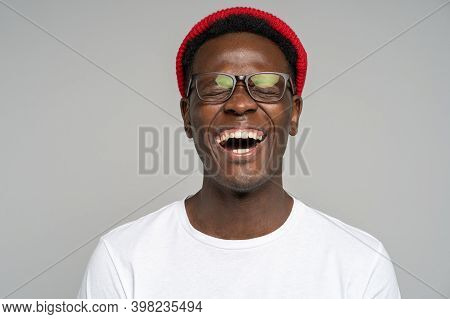 Laughing Positive Young Afro American Man Wear Red Hat In Good Mood, Poses At Camera With Closed Eye