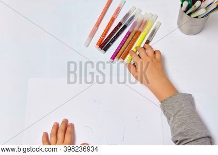 Cute Little Boy With Blond Hair Draws Colored Pencils At Home. Draws At The White Table. Close Up Of