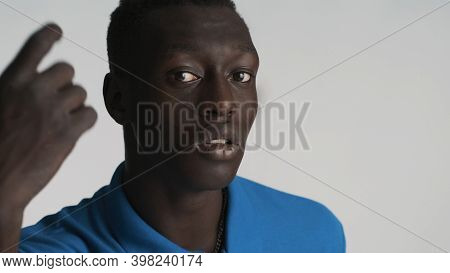 Young African American Man Intently Looking In Camera Over White Background. Come On