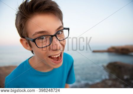 Funny young happy teen boy makes faces with open mouth at beach at the evening, wide angle.