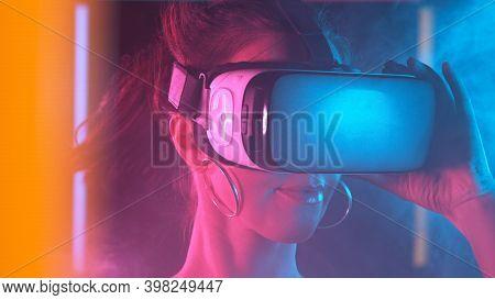 Woman is using virtual reality headset. Neon light studio portrait. Concept of virtual reality.