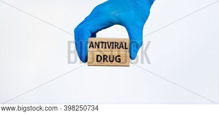 Antiviral Drug Symbol. Hand In Blue Glove Holds Wooden Blocks With Words 'antiviral Drug'. Beautiful