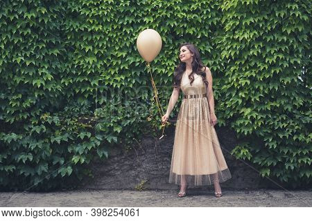 Teen Girl In Glamorous Golden Dress Standing By The Green Wall Holding Balloon. Ready For Her Prom O