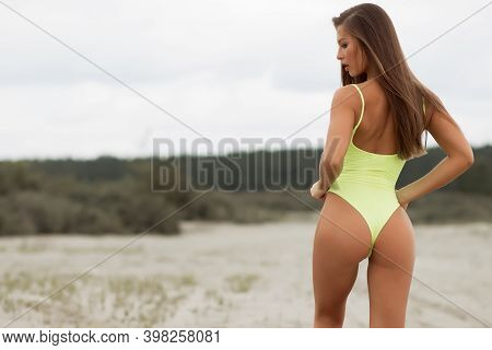 Alluring Shaped Woman With Long Hair Wearing Yellow Bodysuit Standing On Blurred Nature Background A