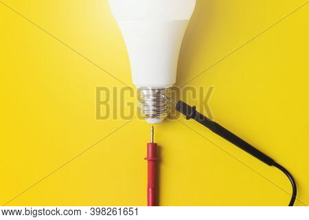 Vital Energy Concept. Light Bulb With Multimeter Probes On A Yellow Background. Technology Concept.