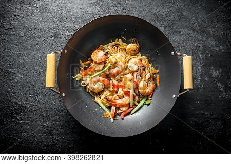 Chinese Wok. Asian Udon Noodles With Shrimp And Vegetables. On Black Rustic Background