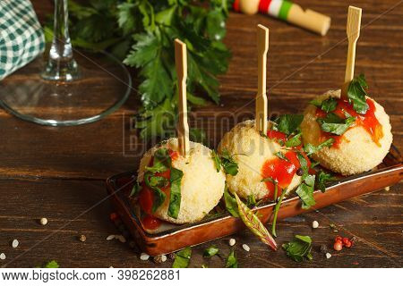 Arancini, Rice Balls With Cheese With Different Fillings Inside. On A Serving Plate With Wooden Skew
