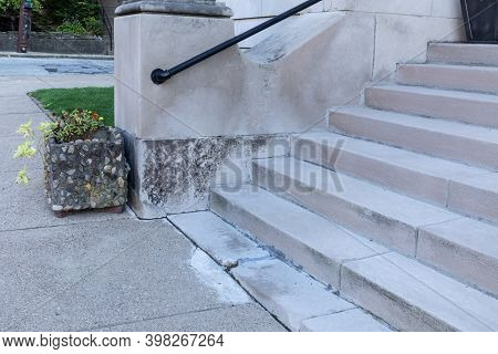 Wide Concrete Entry Stairs On A Church Exterior, Black Metal Pipe Railing And Stone Planter Alongsid