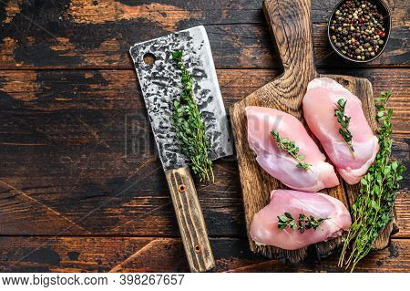 Raw Chicken Skinless Thigh Fillet On A Wooden Cutting Board. Black Background. Top View. Copy Space