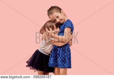 Two Little Cute Girls Sisters Hug Tightly. The Concept Of Love For Relatives.
