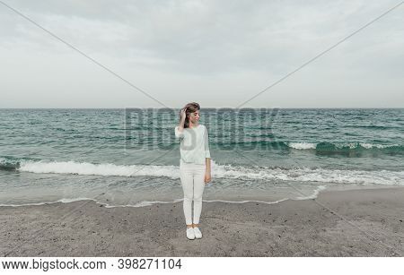 Portrait Of An Amazing Young Girl Standing On An Empty Beach Against The Backdrop Of The Black Sea D